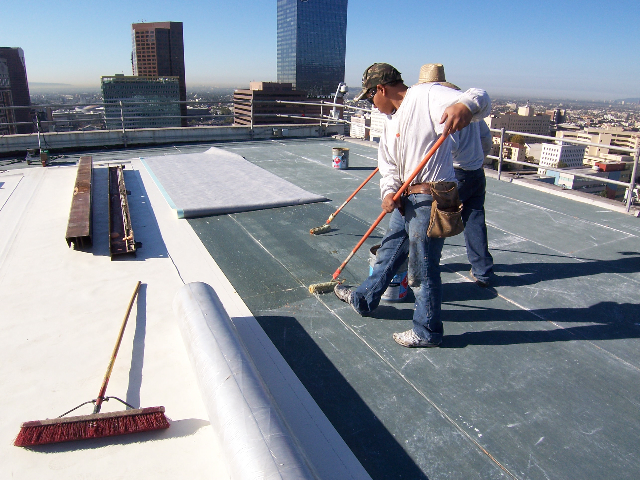 A roofer on a skyscraper working for Augustino Brothers Inc